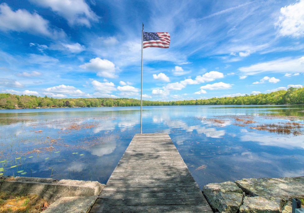 lake with blues skies and an american flag